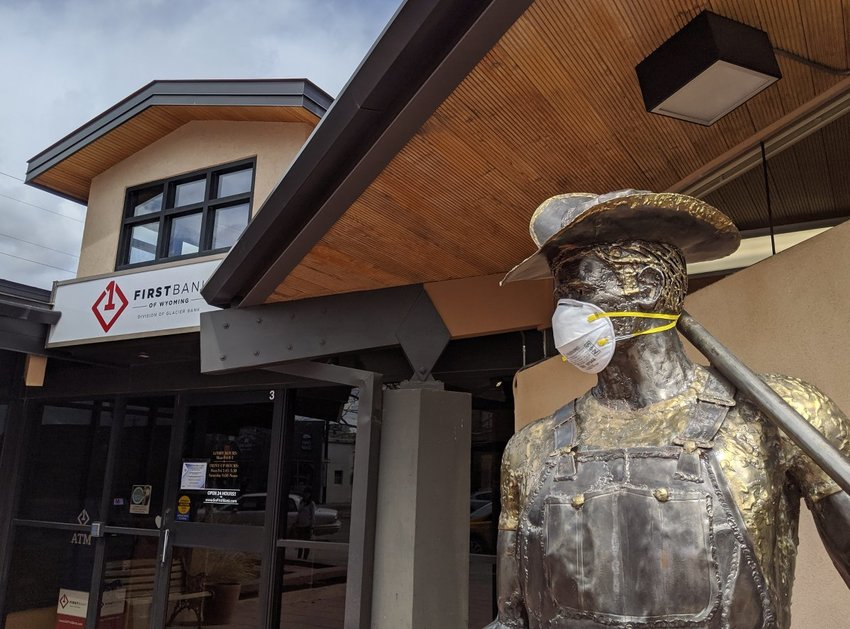 The 'Desert Redeemer' outside the Powell First Bank wears a mask as a reference to COVID-19-related precautions. The state plans to begin easing up on some restrictions starting on Friday, while continuing others.