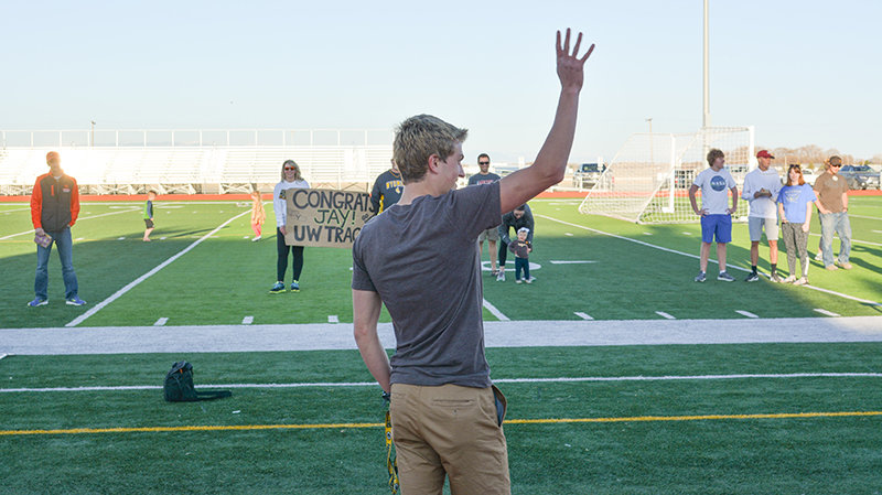 From a safe distance, Jay Cox waves to a group of people who came out to support him on Tuesday night at Panther Stadium, as he signed to join the University of Wyoming track team next school year.