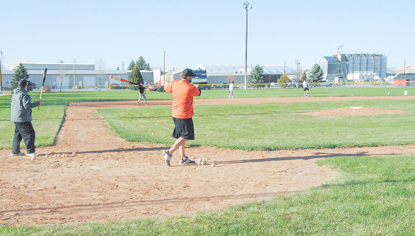 Powell Pioneers coach Joe Cates (right) and assistant coach Ryan Brown do double duty on either side of the plate, hitting ground balls to infielders during a Tuesday afternoon baseball practice.