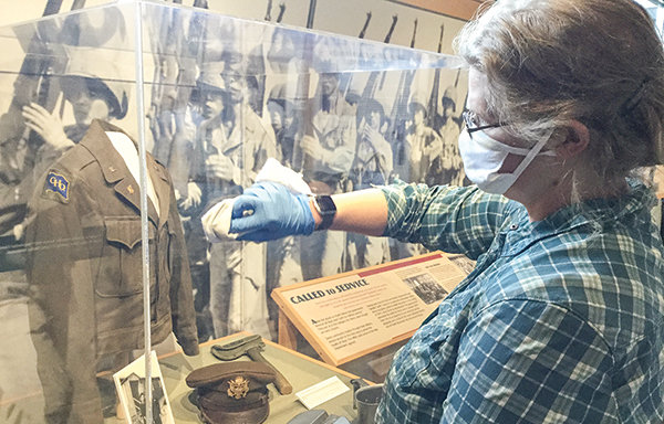 Museum manager Cally Steussy sanitizes an exhibit case at Heart Mountain Interpretive Center in preparation for reopening.