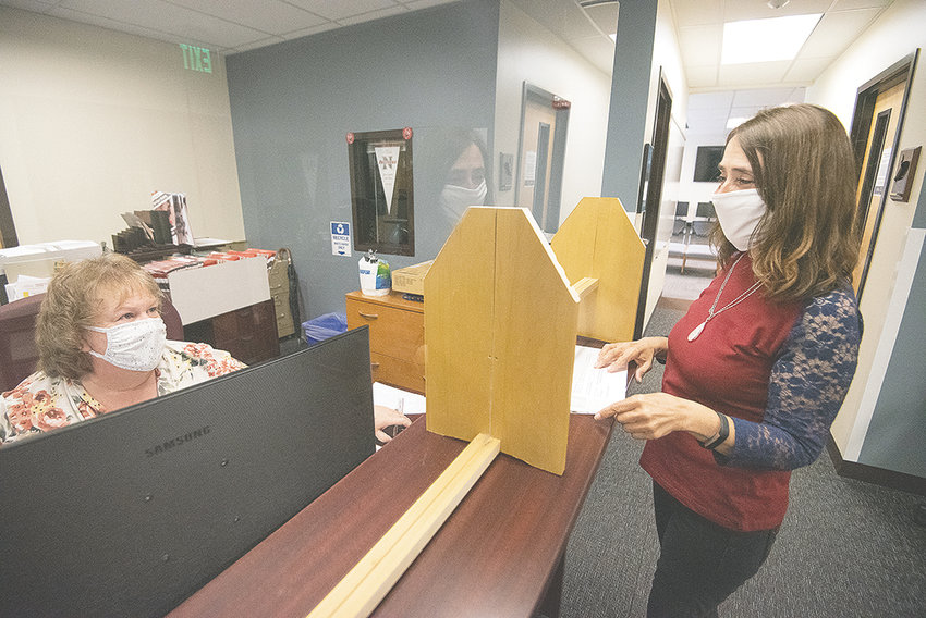 Charlene Kline (left) and Carle Williams work together in the NWC admissions office on Wednesday afternoon. The college adopted a plan this week for fall, which will require all students, faculty and staff to wear masks in most situations on campus.