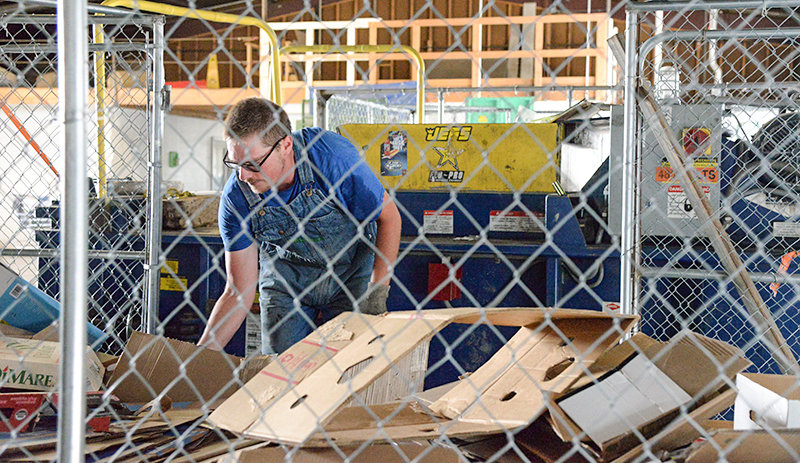 Powell Valley Recycling Center employee Dustin Curtis loads cardboard into the compressor on Tuesday afternoon. The center used to take pasteboard, but the processor will no longer accept it, so employees must ensure none gets into the bales.