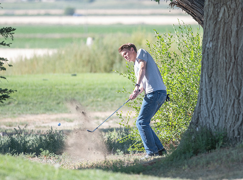 George Higgins hits a shot out of the rough and onto the green at Powell Golf Club on Monday. A senior, Higgins is following up a 2019 campaign in which he finished sixth at the state tournament.