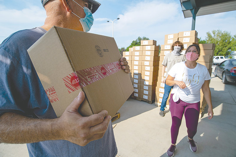 Volunteer Jim Marquez helps load boxes of meat with his daughter, Jeanette Marquez, and Killian Marroquin. Hundreds of area residents waited in line for the free boxes of meat and cheese distributed at Glad Tidings Assembly of God Church Tuesday.