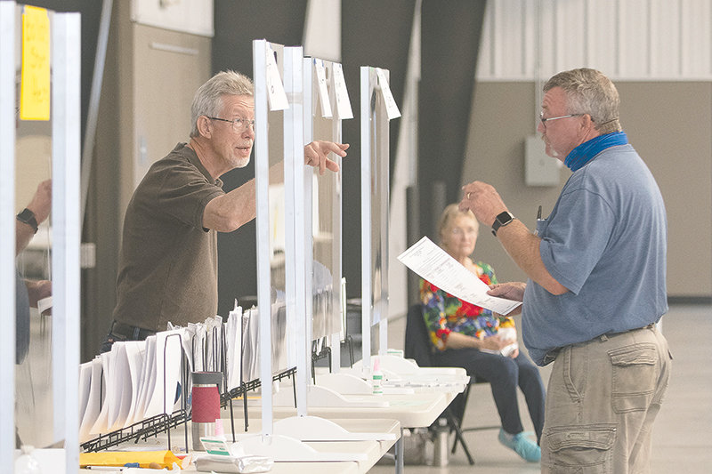 Election official Howard Haun (left) directs Nevin Jacobs to the next station at the Park County Fairgrounds after he received his ballot for Tuesday's primary election. The county consolidated polling places to four locations in Cody, Powell and Meeteetse.