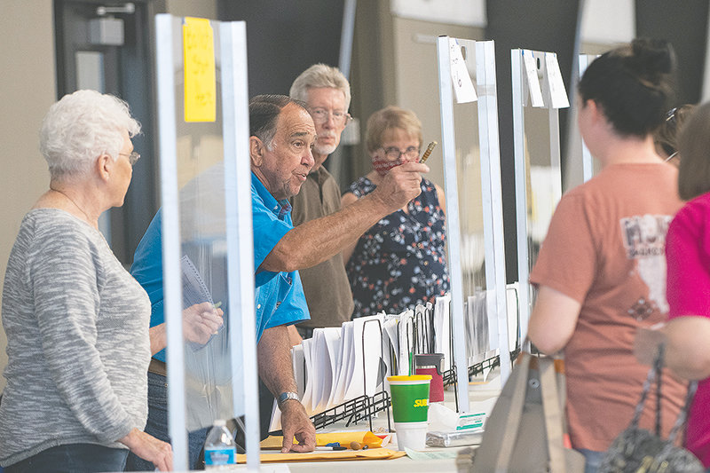Election judge Jacob Dillinger (at left) visits with a voter during the Aug. 18 primary election at the Park County Fairgrounds. At an Aug. 19 county commission meeting — in which multiple citizens expressed opposition to closing several rural polling places for the general election — Dillinger shared frustration with the election process. Clerk Colleen Renner said she's addressing his concerns and commissioners are now set to reconsider the polling places on Sept. 15.