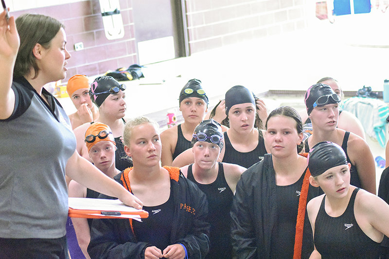 PHS assistant swim coach Bailey Jackson speaks with her athletes at the Riverton Pentathlon. In total, the team achieved 24 state cuts. From left, Dakota Hansen (in back), Emma Brence, Emma Bucher, Lucia Harder, Kylie Kahl, Kathryn Brence, Addison Moretti, Gabby Patterson, Sarah Miller and Paige Thomas.