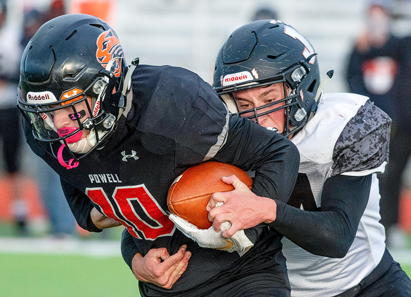 Jackson's William Pew (54) strips the ball from Powell quarterback Landon Lengfelder (10) with 1:10 left in the first half. The fumble was recovered by Jackson and led to a touchdown, changing the momentum of the game.