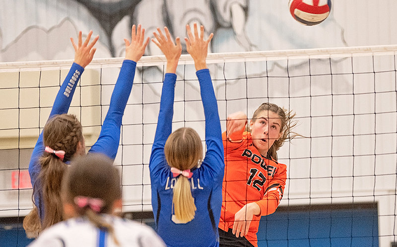 Panther sophomore Megan Jacobsen spikes the ball around two Bulldogs blockers last month in Lovell. The Panthers won this junior varsity contest.