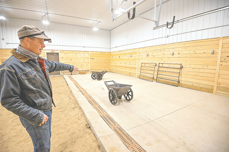 Bryce Meyer, the agriculture and welding teacher at Powell High School shows off the new livestock facility at the school. The building is largely completed, but plans are to build permanent pens on the concrete portion of the arena. There will also be a livestock handling alley and squeeze chute in the building.