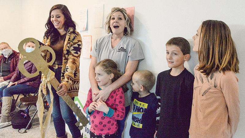 At the Mountain Spirit Habitat for Humanity dedication ceremony, Executive Director Nikki Hoellwarth hands a gold key over to Beth Jolley, symbolizing the mother taking possession of her new home. With Jolley are four of her six children: Brooklyn, Hunter, Garrett and Tayla.