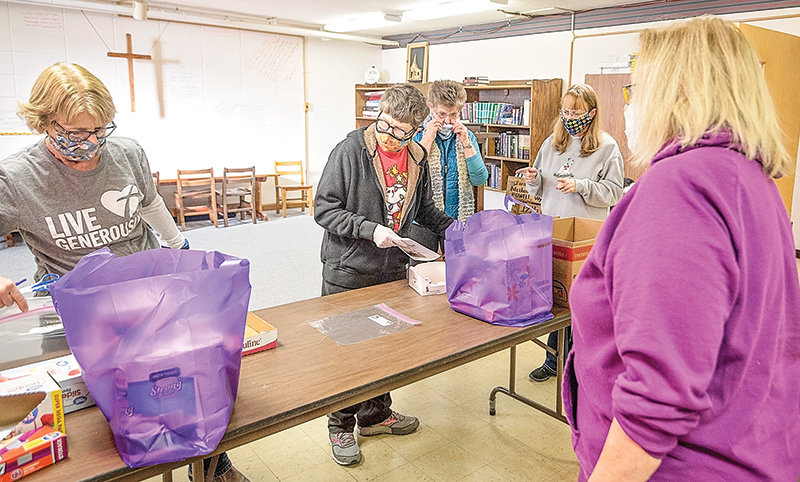 Volunteers from the Homebound Senior Essentials package items into the group's signature purple bags that they deliver to seniors in need. Shown are from left, Bonnie Fauskee, Mary Ann Mertz, Linda Emery, Diane Hensman and Sonja Black (in foreground).