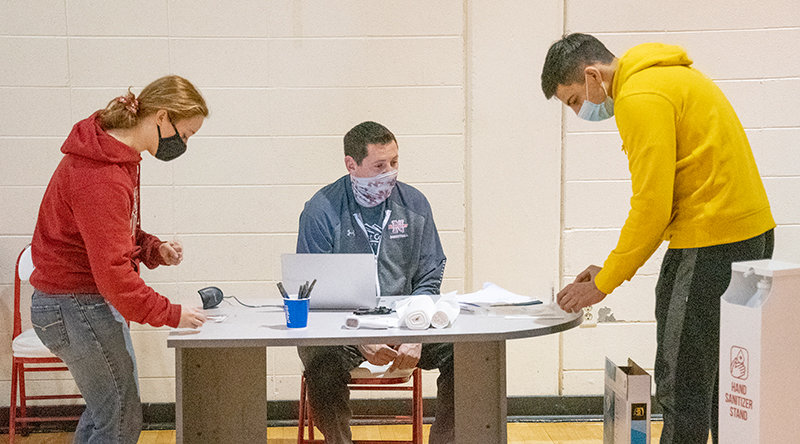 Student training assistant Rebecca Brantz and men's basketball player Gabriel Gutierrez receive their COVID-19 tests from Brian Erickson (center) at Northwest College's Cabre Gym. The school tested all of its student-athletes last week as they returned to campus.