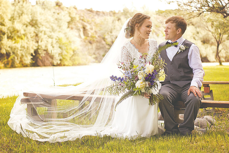 Bride and groom, Amanda and Colin Harnish, posed on their wedding day in June of 2020, seated on a bench in the riverside setting on the banks of the Shoshone River south of Powell.