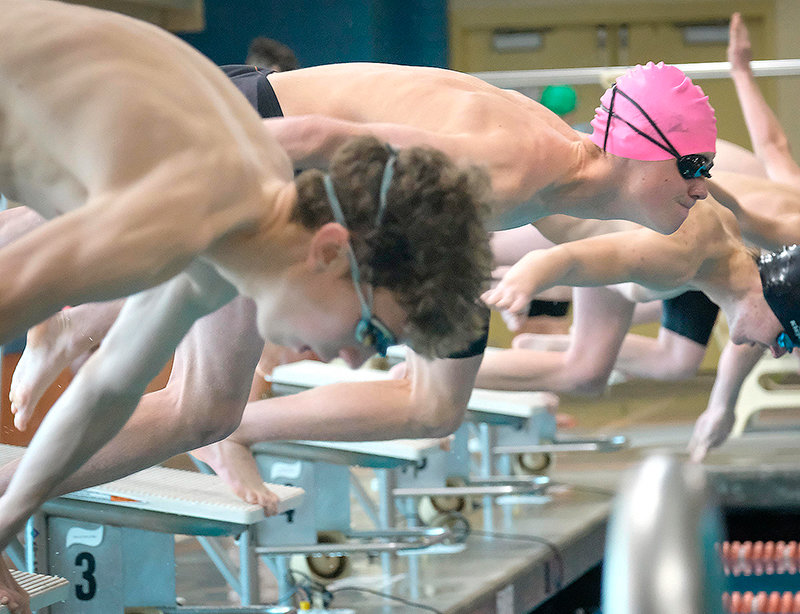 Panther swimmer Ashtin Prentiss (pink cap) leaps from the starting blocks at a recent meet in Worland. Competing in Buffalo Friday, Prentiss grabbed a state-qualifying time in the 200 individual medley and finished the event third overall. The Panthers' next action is the 3A West Conference Championship Saturday in Lander.