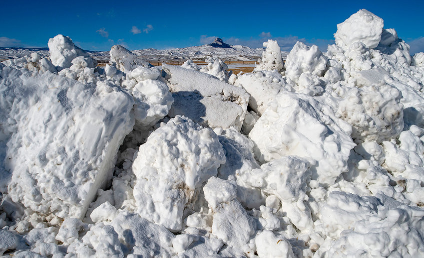 Deep mounds of snow cleared from drifts on Road 19 frame Heart Mountain on Tuesday. Strong winds created whiteout conditions and drifts so deep that school was canceled in Powell on Monday.