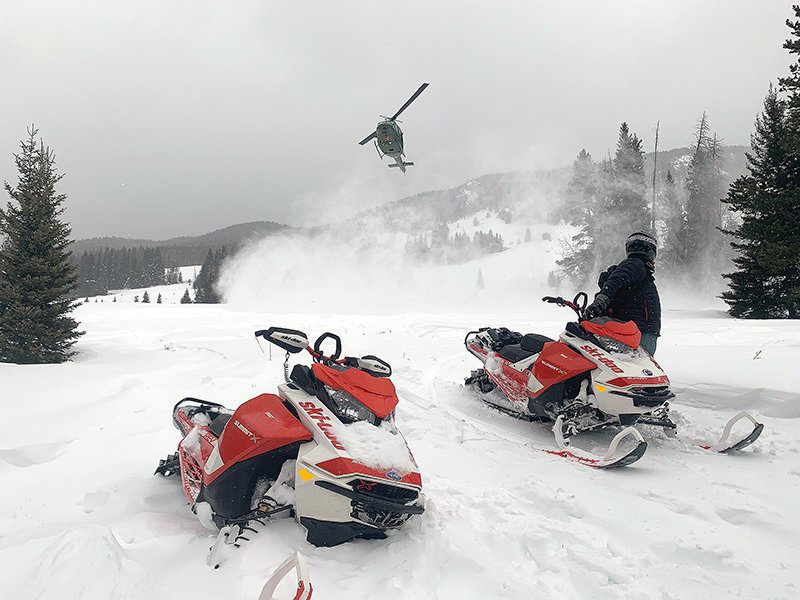 A helicopter lifts off Saturday with two men who were rescued after being lost in the Beartooth Mountains for two days. Multiple agencies and volunteers from the community helped save the Montana snowmobilers.