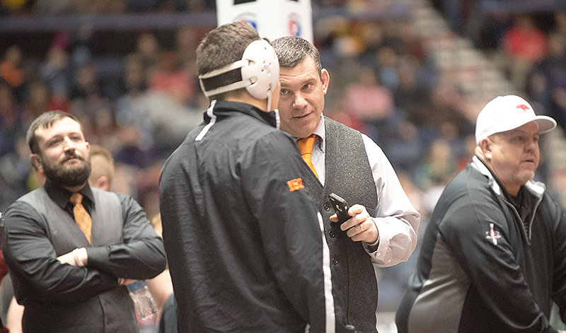Coach Nate Urbach talks to Brody Karhu before a match at the 2019 State Wrestling Championships. Urbach led Powell High School to six state titles in his career.
