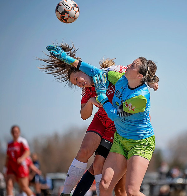 Goalkeeper Alexa Williams hits a ball away in Northwest College's Saturday match against Otero and collides with teammate Shyley Hunter, who was defending. Despite falling to the Rattlers, the Trappers scored their first goal of the year when Kierra Cutright cashed in on a corner kick.