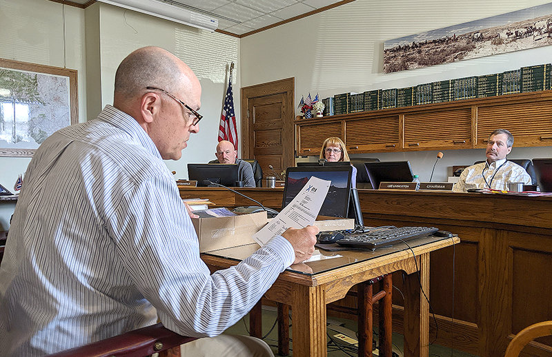 First Deputy Park County Clerk Hans Odde opens a proposal from Arete Design Group of Sheridan — one of three architects to formally express interest in designing a renovated Powell Library — at the April 20 county commission meeting. The proposals are now being reviewed.