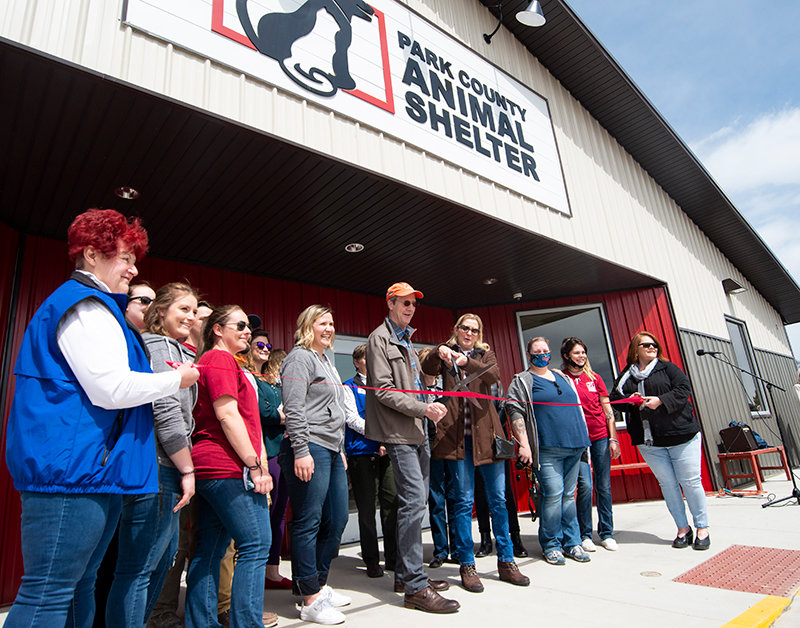 Former Park County Animal Shelter board president Ken Markert and fundraiser Lani Snyder cut the ribbon during the grand opening of the new facility, while executive director Megan McLean, employees and volunteers look on. The $2.2 million facility officially opened to the public Saturday.