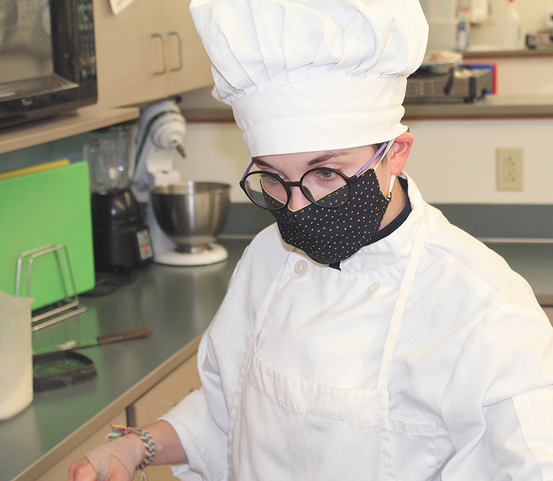 Maggie Cappiello concentrates on a recipe for cupcakes in the SkillsUSA lab at Powell HIgh School.