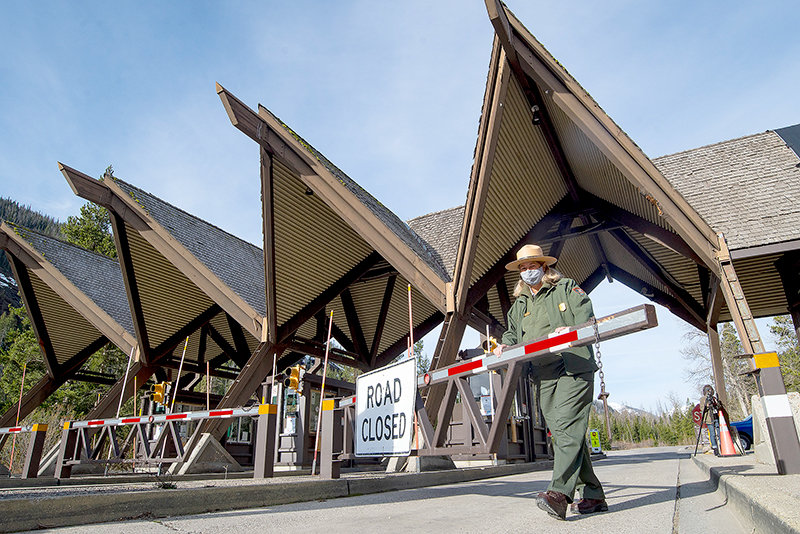 Yellowstone National Park Ranger Kimberly Kain swings open the East Entrance gates at 8 a.m. Friday for the summer season. Almost a mile of cars were in line, with it taking nearly an hour to clear the congestion for motorists eager to get inside.