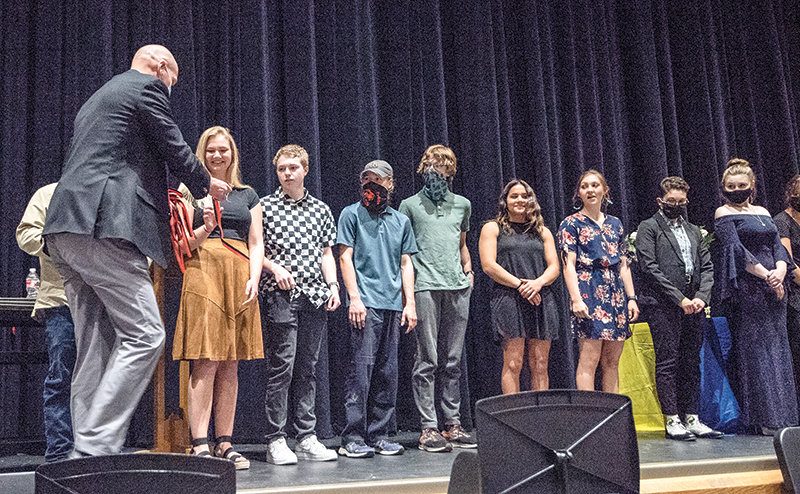 Powell High School principal Tim Wormald hands out medallions to senior National Honor Society members last month during the induction ceremony. From left are Whitney Hull, Averee Johnson, Isaac Summers, Riley McKeen, Emma Karhu, Jozi Simpson, Maggie Cappiello and Bailey Phillips.
