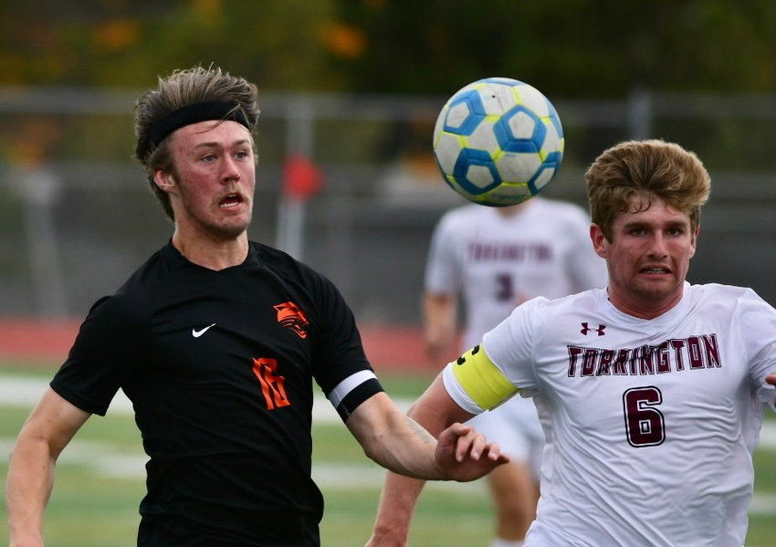 Sam Bauer tracks down a ball in Friday's semifinal game against Torrington, running alongside Trailblazer Adam Bartlett. The Panthers scored the match's last three goals to earn the come-from-behind, 3-1 win.