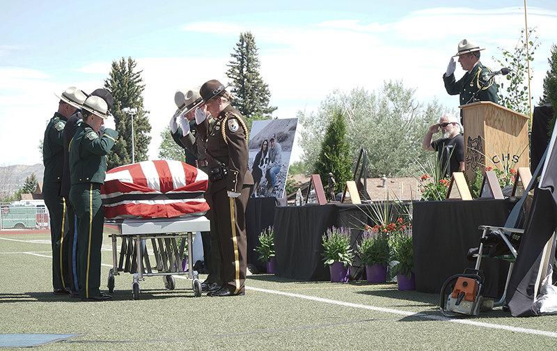 Members of the U.S. Department of Agriculture Forest Service Honor Guard salute smokejumper Tim Hart's flag-draped casket during a Friday memorial service at Cody's Spike Vannoy Field.