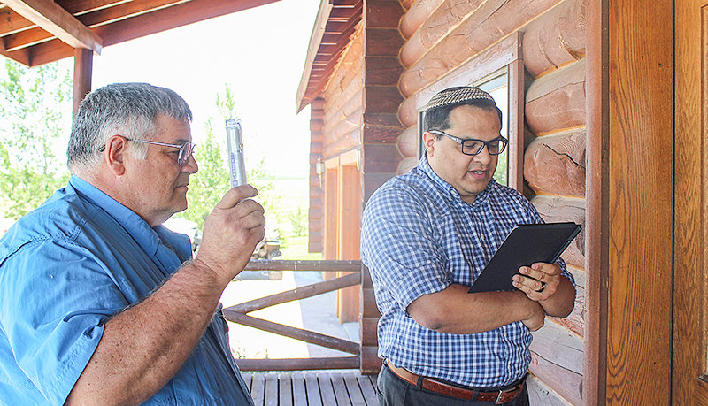 Powell resident Scott Hecht (left) holds the mezuzah he will soon afix to his door frame while Rabbi Erik Uriarte reads a Jewish prayer as part of the ancient ritual.