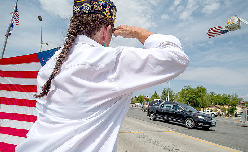 Katy Jones, vice commander of American Legion Post 26, salutes as the hearse carrying Worland native and Vietnam veteran Alva R. Krogman passed through Frannie Monday. After being shot down over Laos in 1967, Krogman's remains were returned to Worland and his final resting place this week.