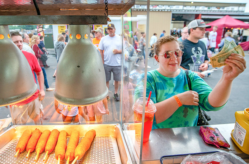 Destiny Stuebner, of Powell, pays for her carnival food at the Park County Fair Friday night. Many vendors saw strong sales this year, according to fair organizers.