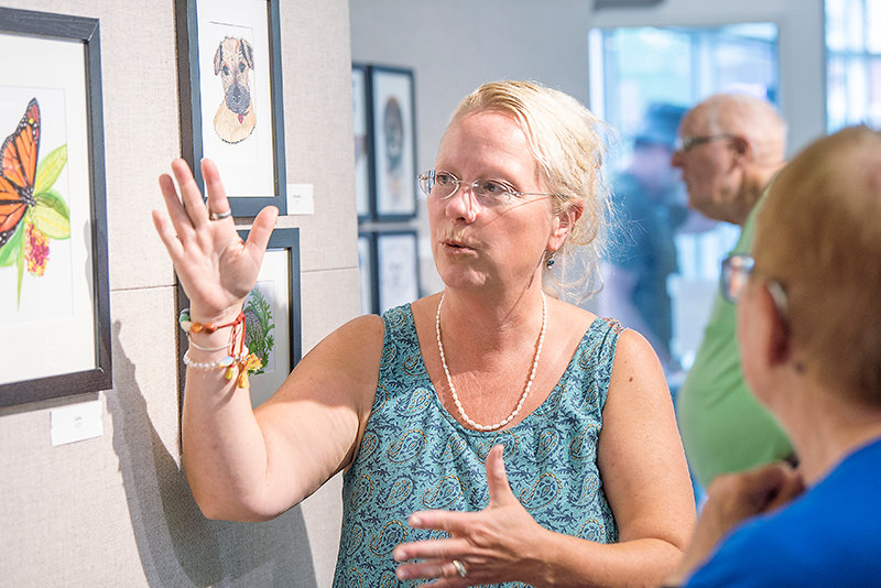 Powell artist Justine Larsen visits with attendees at the July 15 opening of her exhibit, 'Birds, Bees, & Beasts,' at Plaza Diane. The show will be on display through Saturday.