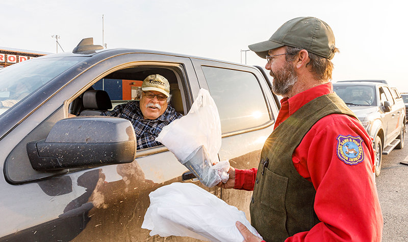 Luke Ellsbury of the Wyoming Game and Fish Department (at right) hands out a complimentary can of bear spray during a giveaway last year. The department will distribute another 115 cans of spray to hunters and anglers on Monday, Aug. 30 in Cody.