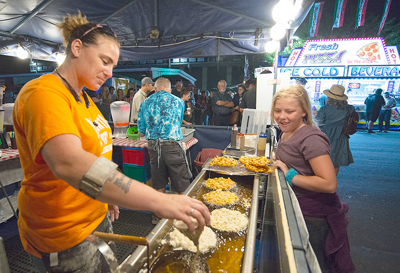 Tessa Bechtold, of Cheyenne, makes funnel cakes while her daughter, Abby, watches on. The 2021 Park County Fair was reportedly a strong one for vendors, with the carnival seeing particularly long lines. Three of the grandstand events also drew big crowds, while the other two events had smaller audiences.