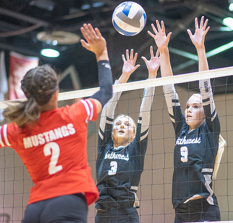 Northwest College's Sayler Larson (center) and Sidney Parker (right) look to stuff a shot during a home match against Western Wyoming Community College last month. The Trappers continued their winning ways last weekend in Idaho.