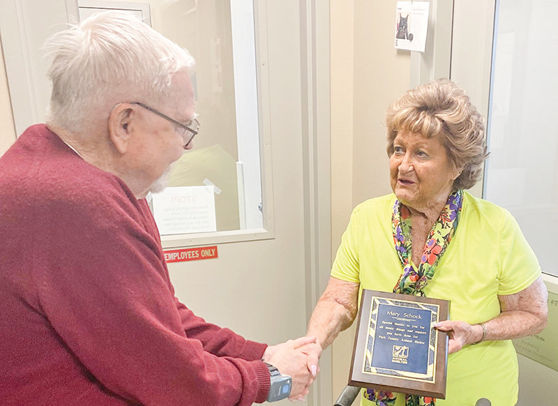 Longtime Park County Animal Shelter supporter and board member Mary Schock (at right) receives an honorary award from current board of directors member Bob Stevens.