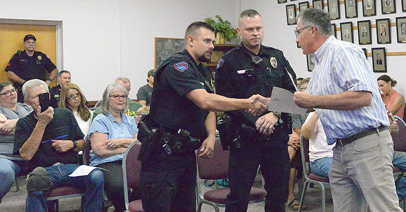 Powell Mayor John Wetzel shakes the hand of Powell Police Officer Kevin Bennett as fellow Officer Ryan Davis looks on at the Powell City Council's Sept. 7 meeting. Davis and Bennett were being honored for their quick actions, which were credited with helping to save the life of a local resident last month.