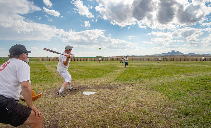 Frank Fagan, pitcher for the One Hit Wonders, gets ready to hit the ball in a losing effort against the Buds during a Saturday game in the loser's bracket of the Field of Dreams Softball Tournament. Heart Mountain was a target in the background.