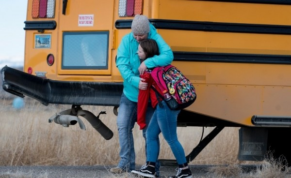 A mother comforts her child on Monday afternoon after a Powell school bus was hit by a pickup at the intersection of Lane 5 and Road 8. The bus was involved in another crash earlier in the day.