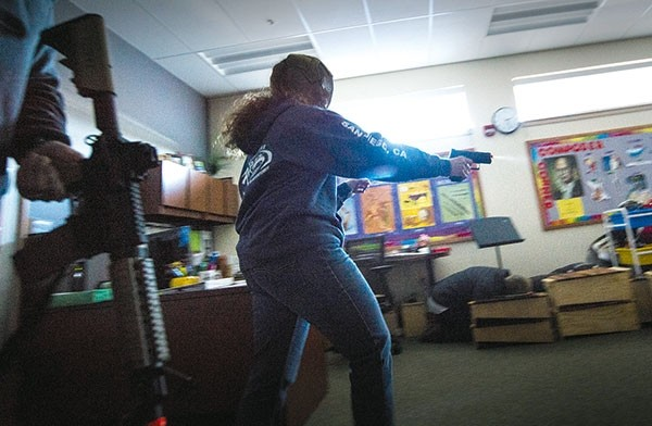 Armed with an Airsoft handgun, Westside Elementary teacher Donna Cole plays the role of a shooter during an ALICE training drill the school held Wednesday. The training is one way that the Powell school district works to protect students. District leaders are considering the possibility of allowing trained staff to carry firearms as another precaution.