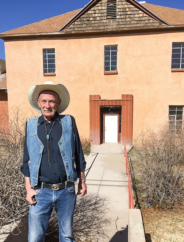 Flint Carter of Oracle, Arizona, stands in front of the former Mountain View Hotel, built in 1895. Buffalo Bill Cody was said to be an owner. The porch has been removed from the two-story stucco building, and it sags in disuse. The property is owned by the Southern Baptist Church there.