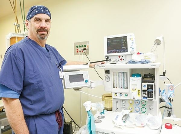 Stephen Katz, a nurse anesthetist at Powell Valley Healthcare, stands beside the machine he uses to anesthetize patients during surgery. The display on the left tracks oxygen; the one on top monitors the heart, and the tubes underneath control the mix of oxygen and anesthesia, with additional dials performing other functions. Being an anesthetist 'is a highly technical job,' Katz said.