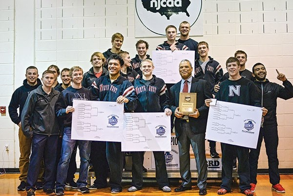 Trapper wrestlers and coaches pose at the podium after the announcement that Northwest College was the champion at the NJCAA Rocky Mountain District National Qualifier at home on Feb. 11.