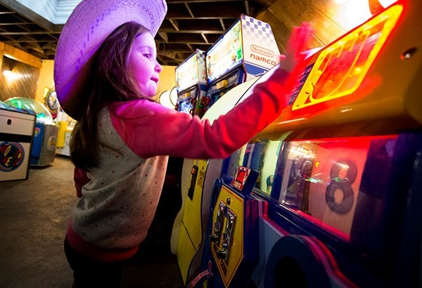 Nova Burbank plays a carnival game in the Millstone Pizza and Brewery arcade on Tuesday evening. Powell's City Council plans to repeal an ordinance that has required businesses to pay an annual $3 fee on pool tables and other games.