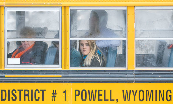 Georgia Rutschke, a special education teacher at Powell High School, and student Kayla Streeter watch from the school bus as Wyoming Game and Fish employees process bighorn sheep at the Bighorn Canyon National Recreation Area.