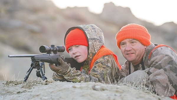 Shelby Fagan and her father Frank, both of Powell, check the status of her harvested deer through the scope after Shelby pulled the trigger on her first big game animal.