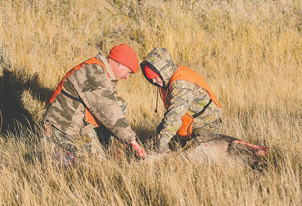 Frank Fagan and his daughter Shelby field dress a doe Shelby harvested — her first.