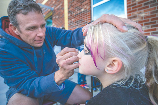 Crosby Tajan, a teacher at Powell Middle School, paints 11-year-old Taylor Iverson's face during the Harvest Festival.